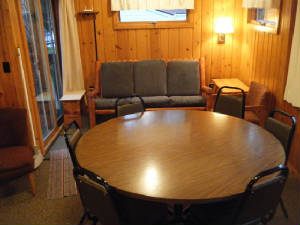 Dining Table in a great location near the kitchen & Patio Door.  Log Couch adjacent to the Deck with picnic table
