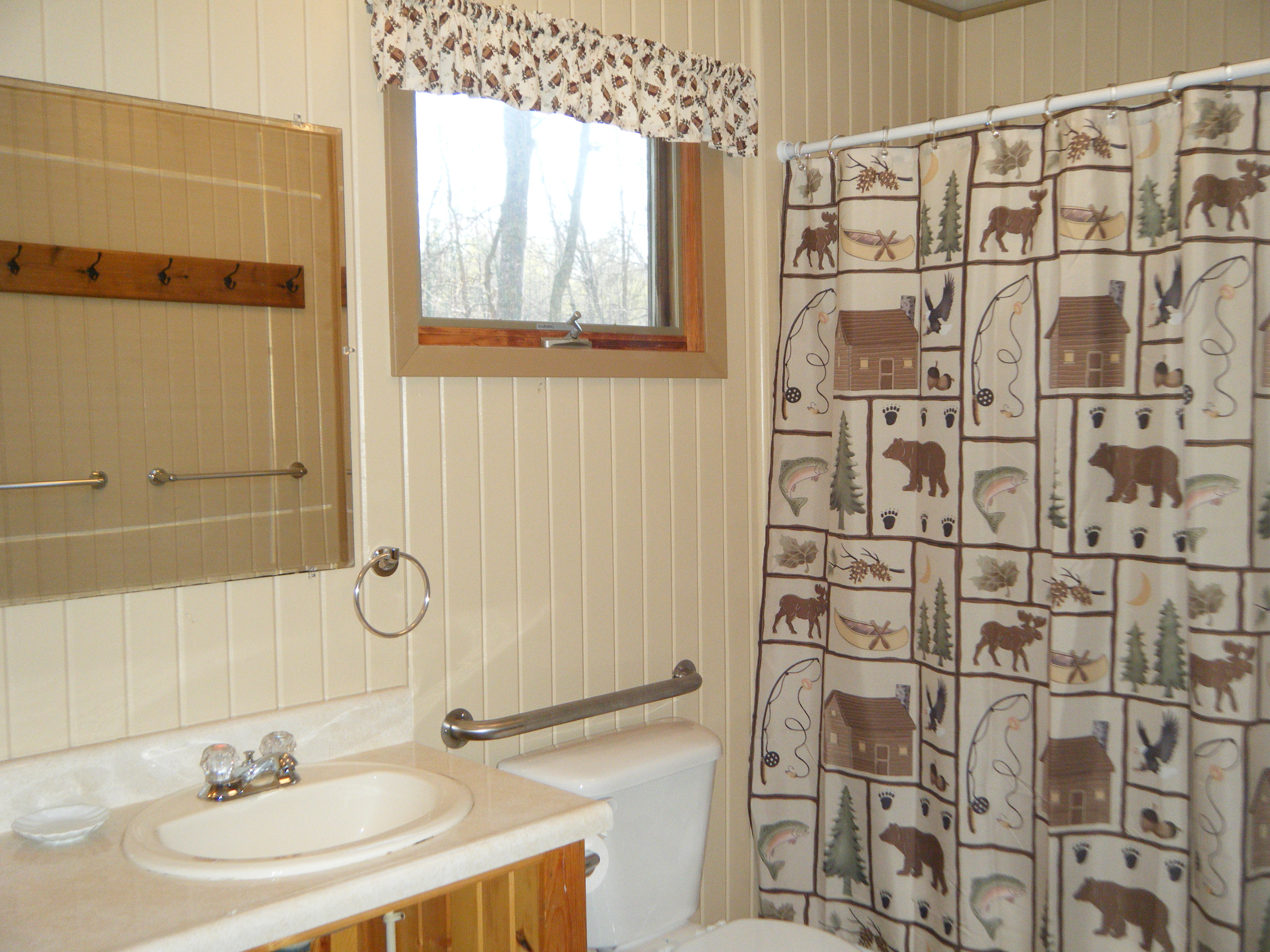 "Cabin #15's main bathroom with tub/shower combination & decorated in ""Up North' theme.  2nd bathroom is located off of the dining area."