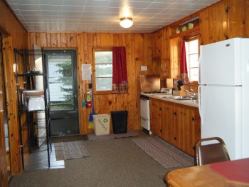Cabin 8 kitchen is full stocked with pots/pans, dishes, silverware & full size appliances.  Kitchen leads into Dining area.