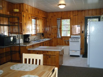 Cabin 6 Kitchen stocked with pots, pans, dishes, coffee pot, microwave, and full size appliances