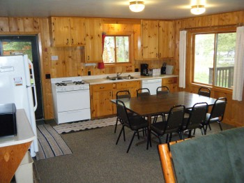 Cabin #15 kitchen fully stocked with dishes, pots/pans, and full size appliances plus a Microwave, dishwasher, & coffee pot.